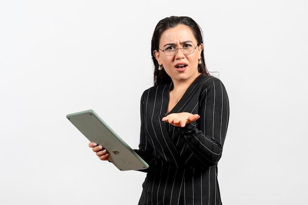 Vista frontale giovane donna in abito scuro rigoroso che tiene grande calcolatrice su sfondo bianco lavoro donna signora moda lavoratore bellezza