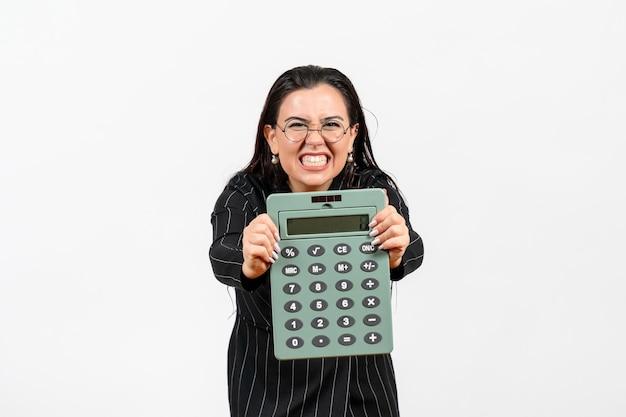 Vista frontale giovane donna in abito scuro rigoroso che tiene grande calcolatrice su sfondo bianco ufficio bellezza affari lavoro moda donna
