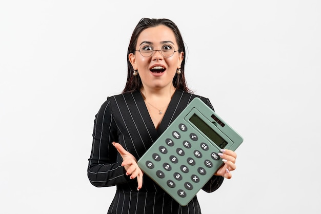 Front view young woman in dark strict suit holding big calculator on white background office beauty business job fashion female