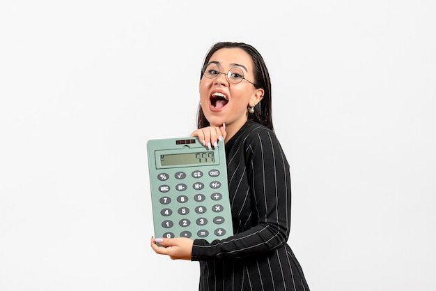 Front view young woman in dark strict suit holding big calculator on white desk job woman lady fashion worker beauty