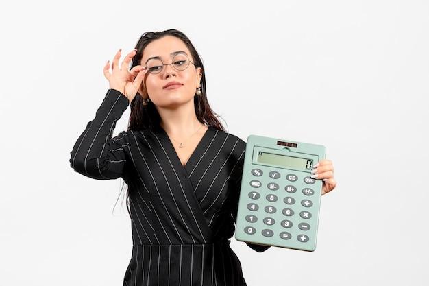 Giovane donna di vista frontale in vestito rigoroso scuro che tiene grande calcolatrice sul lavoro d'ufficio di affari di moda della donna di bellezza del pavimento bianco