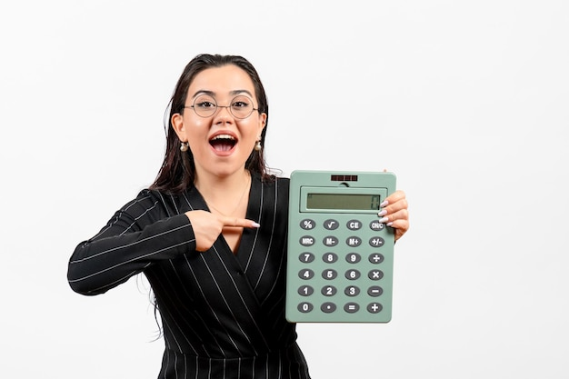 Front view young woman in dark strict suit holding calculator on a white background job woman fashion business beauty office
