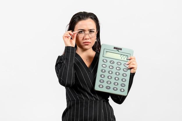 Vista frontale giovane donna in abito rigoroso scuro che tiene calcolatrice su sfondo bianco lavoro donna moda affari bellezza ufficio