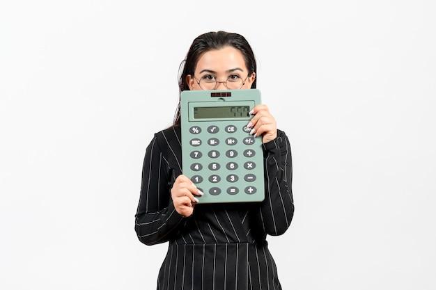 Vista frontale giovane donna in abito rigoroso scuro che tiene calcolatrice su sfondo bianco lavoro donna ufficio moda affari bellezza