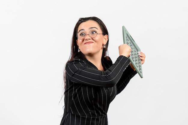 Vista frontale giovane donna in abito rigoroso scuro che tiene calcolatrice su sfondo bianco ufficio bellezza affari lavoro moda femminile