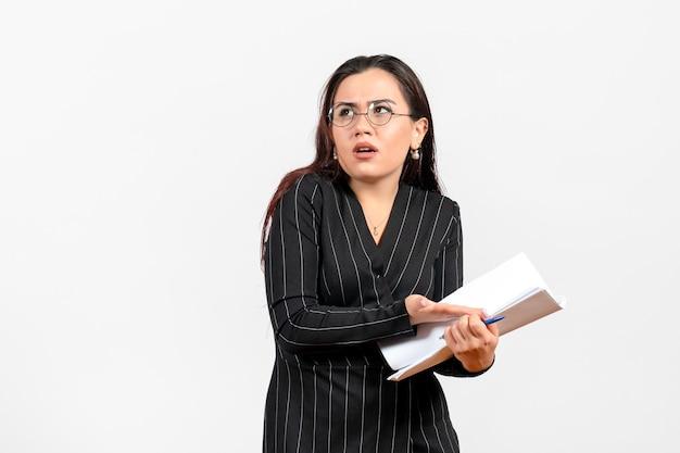 Vista frontale giovane donna in abito scuro rigoroso che tiene e controlla i file su uno sfondo bianco lavoro d'ufficio aziendale documento femminile