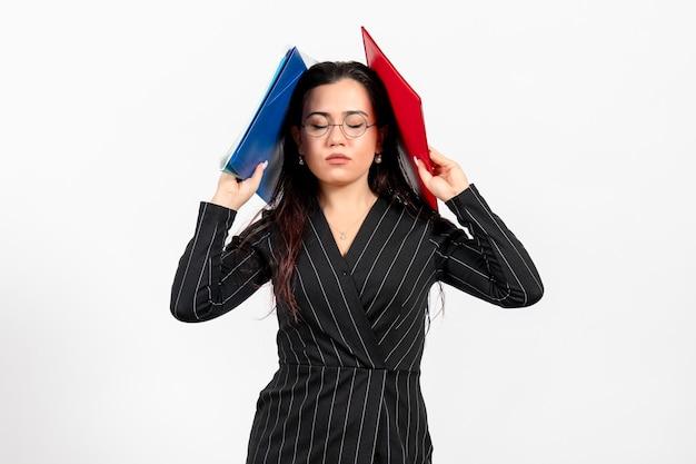 Vista frontale giovane donna in abito scuro rigoroso in possesso di diversi documenti su sfondo bianco lavoro d'ufficio affari documento femminile