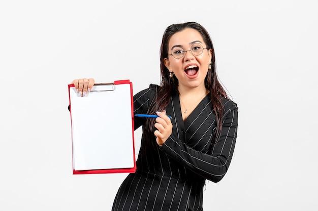 Vista frontale giovane donna in abito scuro rigoroso che tiene documento e penna su sfondo bianco lavoro di documento di ufficio femminile di affari