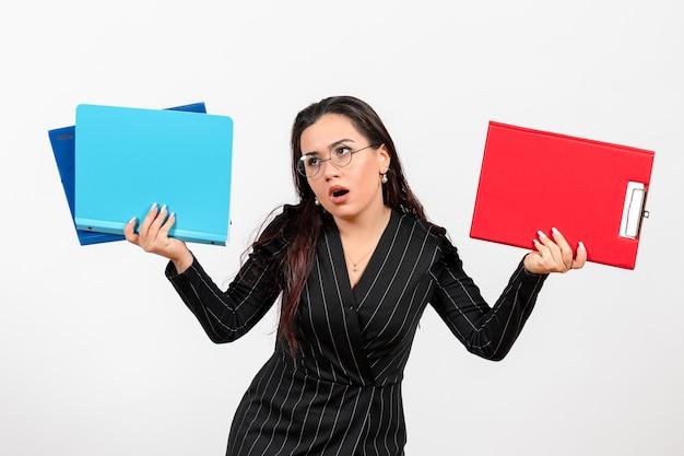 Vista frontale giovane donna in abito scuro rigoroso in possesso di documenti su sfondo bianco documenti femminili lavoro d'ufficio aziendale