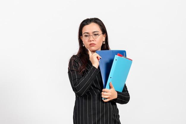 Vista frontale giovane donna in abito scuro rigoroso in possesso di documenti con faccia stressata su sfondo bianco lavoro d'ufficio affari documento femminile