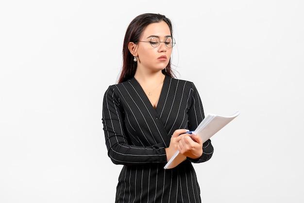 Vista frontale giovane donna in abito scuro rigoroso in possesso di file su sfondo bianco lavoro d'ufficio aziendale documento femminile