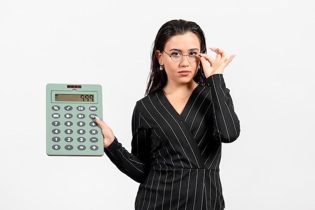 Vista frontale giovane donna in abito scuro rigoroso con enorme calcolatrice su sfondo bianco lavoro donna signora bellezza moda business