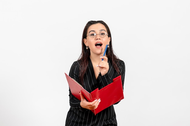 Vista frontale giovane donna in abito scuro rigoroso che tiene file rosso su sfondo bianco ufficio affari lavoro moda femminile documenti