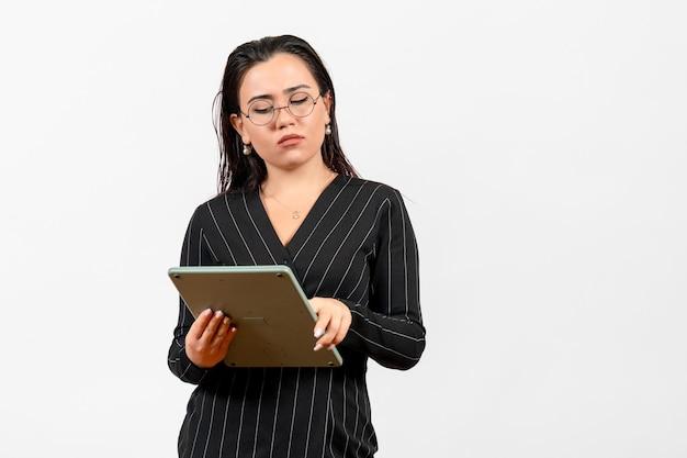 Vista frontale giovane donna in abito scuro rigoroso che lavora con un'enorme calcolatrice su sfondo bianco lavoro donna signora bellezza moda business