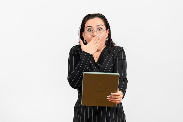 Vista frontale giovane donna in abito scuro rigoroso che lavora con un'enorme calcolatrice su sfondo bianco lavoro donna ufficio moda business beauty