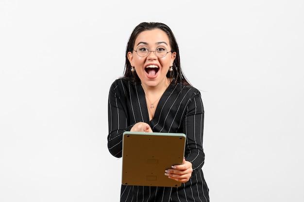 Vista frontale giovane donna in abito scuro rigoroso che lavora con un'enorme calcolatrice su scrivania bianca lavoro donna signora bellezza moda business