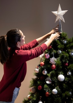 Front view young woman decorating christmas tree
