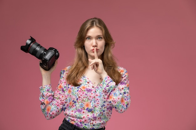 Front view young woman demonstrates silence gesture and photocamera