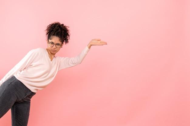 Vista frontale della giovane donna scontenta sulla parete rosa