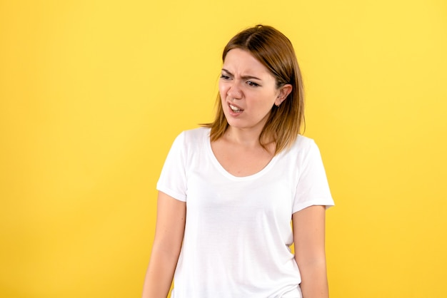 Vista frontale della giovane donna scontenta sulla parete gialla