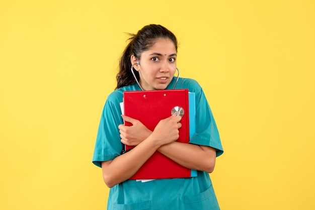 Вид спереди молодая женщина-врач в униформе, держащая красный буфер обмена, стоя на желтом фоне