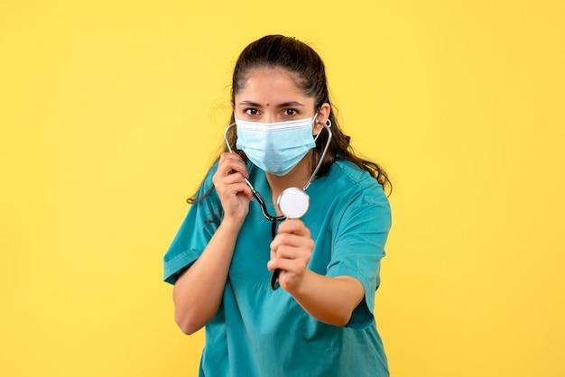 Вид спереди молодая женщина-врач в униформе, держащая стетоскоп, стоя на желтом фоне