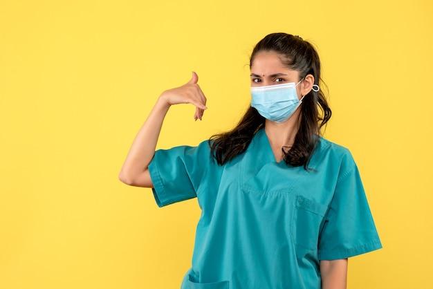 Вид спереди молодая женщина-врач в униформе делает звонок мне телефонный знак, стоящий на желтом фоне