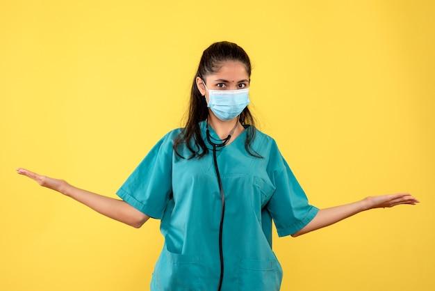 Вид спереди молодая женщина-врач в униформе, открывая руки, широко стоя на желтом фоне
