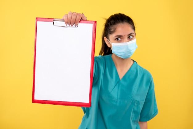 黄色の背景の上に立っているクリップボードを示す制服を着た若い女性医師の正面図