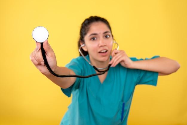 黄色の背景に聴診器を使用して制服を着た若い女性医師の正面図