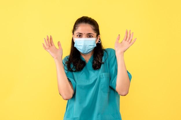 Medico della giovane donna di vista frontale in uniforme che apre le sue mani che stanno su fondo giallo