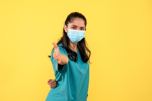 Medico della giovane donna di vista frontale in uniforme che mette una mano dietro la schiena in piedi su sfondo giallo