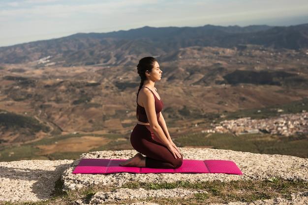 Вид спереди молодая женщина делает йогу