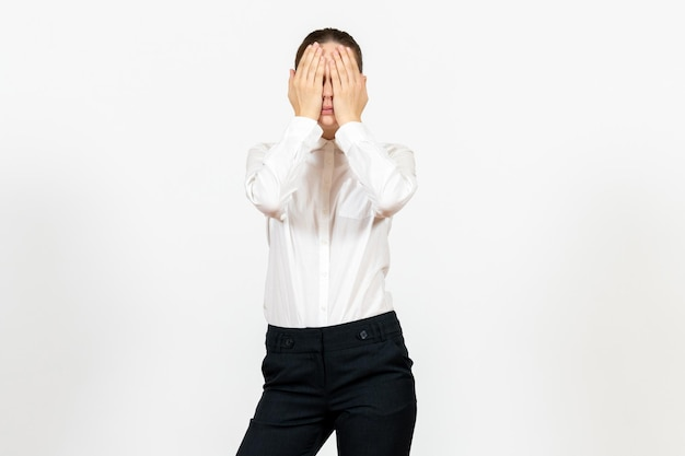 Front view young woman in elegant white blouse covering her face on white background woman office job lady female worker