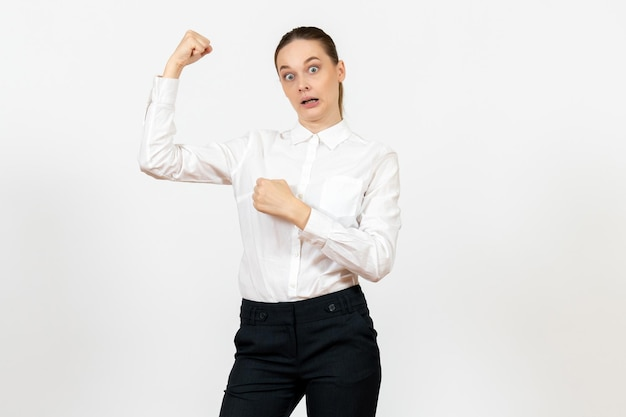 Front view young woman in elegant white blouse flexing on white background woman office job lady female worker