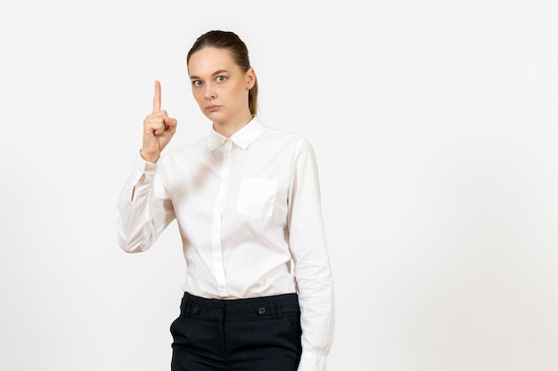 Front view young woman in elegant white blouse standing on white background woman office job female worker lady