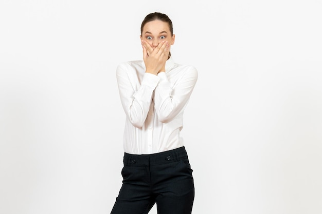 Front view young woman in elegant white blouse with shocked face on a white background woman office job lady female worker