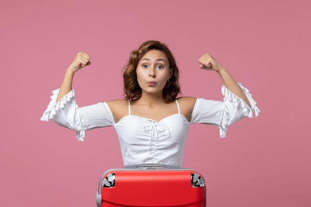 Vista frontale della giovane donna che posa emotivamente sulla parete rosa