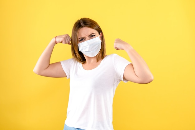 Front view of young woman flexing in mask on yellow wall