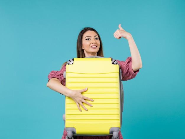 休暇に行くと青い背景の上の大きなバッグを保持している正面図の若い女性夏の旅海の休暇の航海の女性