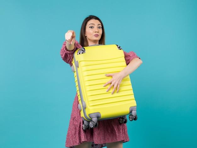 Вид спереди молодая женщина, идущая в отпуск и держащая большую сумку на синем фоне, путешествие на море, отдых, путешествие, женщина