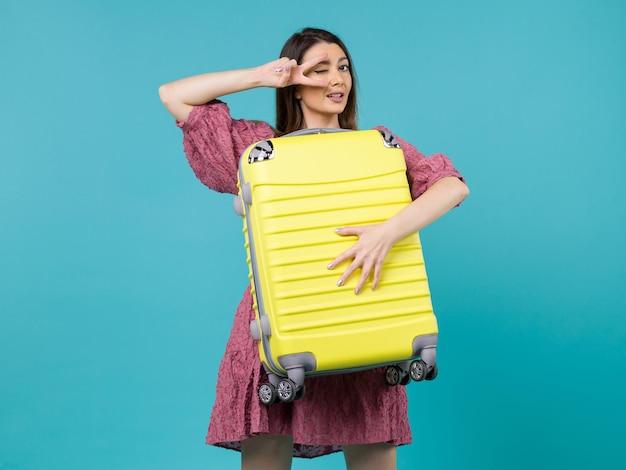 Вид спереди молодая женщина, идущая в отпуск и держащая большую сумку на синем фоне, путешествие на море, отпуск, путешествие женщина за границу
