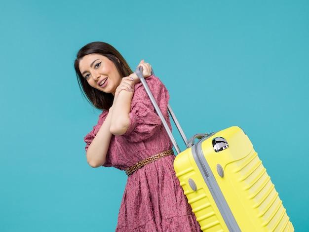 青い背景の旅夏の旅行女性海人間に彼女の大きなバッグと一緒に休暇に行く正面図若い女性