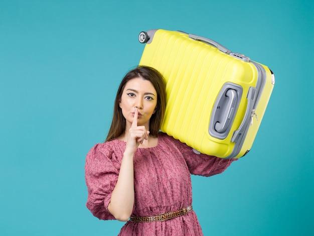 青い背景の上の彼女の大きなバッグと休暇に行く正面図若い女性夏の旅の女性の海の休暇の航海