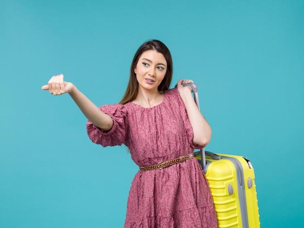 正面図水色の背景の旅の夏の旅行の女性の人間の海に彼女の黄色いバッグと一緒に休暇に行く若い女性
