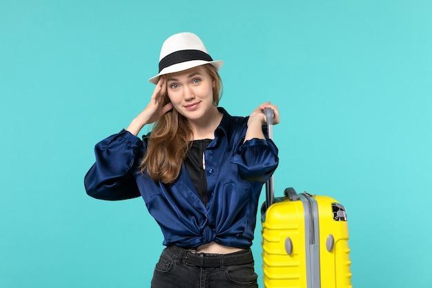 Giovane donna di vista frontale che va in vacanza e che tiene grande borsa sul viaggio di vacanza di viaggio della ragazza del mare di viaggio del fondo blu