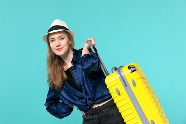 Front view young woman going in vacation and holding big bag on blue desk journey sea vacation voyage travel