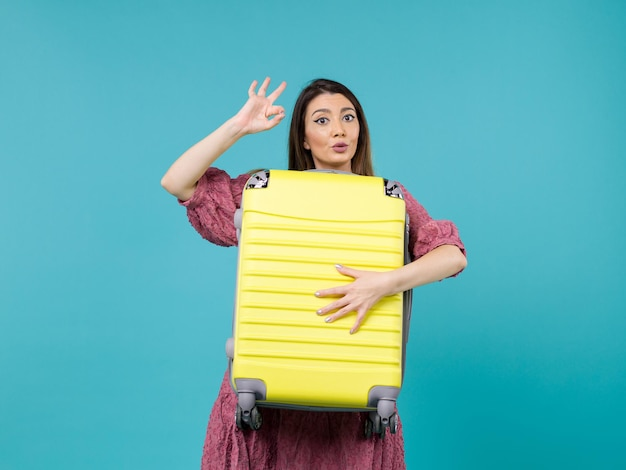 Front view young woman going in vacation and holding big bag on blue desk summer journey sea vacation voyage woman