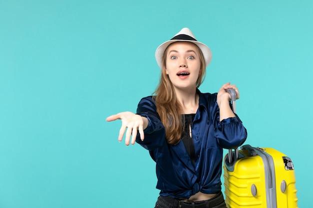 Giovane donna di vista frontale che va in vacanza e che tiene grande borsa sul viaggio di vacanza di viaggio della ragazza del mare di viaggio dello scrittorio blu