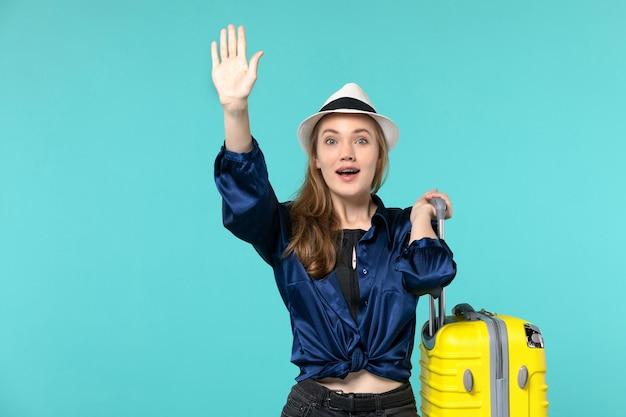 Giovane donna di vista frontale che va in vacanza e che tiene grande borsa sul viaggio di vacanza di viaggio della ragazza del mare di viaggio del pavimento blu